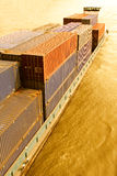 Container Ship at Sunset. A large container cargo ship in a river with warm sunset colors Royalty Free Stock Photo