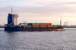 Container Ship At Sunset. Container Ship Leaving the Port of Rotterdam at Sunset. Some industrial Plants are Visible in Background royalty free stock image