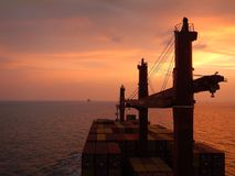 Container ship at the sunset, orange sky Royalty Free Stock Photos
