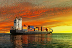 Container Ship. At sunset in the sea Stock Image