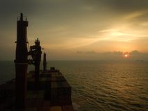 Container ship at the sunset, sun near the horizont royalty free stock images