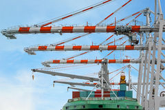 Container Ship in terminal working with shore crane at dock Royalty Free Stock Images