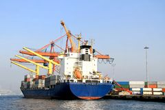 Container ship under loading. Container ship under the colorful cranes at harbor Stock Photo