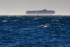 Container ship in the windstorm. A container ship in the gulf of Trieste while a strong wind is blowing Royalty Free Stock Images