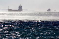 Container ship in the windstorm. Container ships in the gulf of Trieste while a strong wind, known as bora, is blowing at 70 mph Stock Image