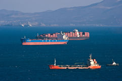 Container ship ZIM Pusan, bulk carrier Hebei Qinhuangdao and tanker Langery anchored in the roads. Nakhodka Bay. East (Japan) Sea. Stock Photos