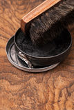Container of shoe polish and brush on wooden Stock Image
