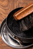 Container of shoe polish and brush on wooden Stock Images