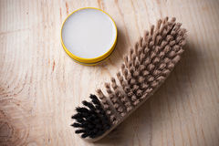 Container of shoe polish and brush on wooden background Royalty Free Stock Image