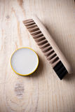 Container of shoe polish and brush on wooden background Royalty Free Stock Photos