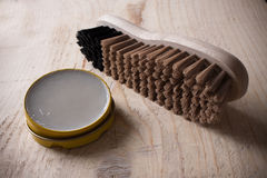 Container of shoe polish and brush on wooden background Stock Images