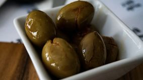 Container of spicy green olives royalty free stock image