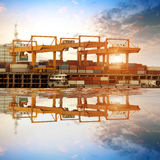 Container stacks and ship under crane bridge Stock Image