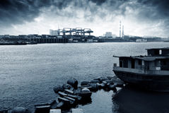Container stacks and ship under crane bridge Royalty Free Stock Image