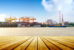 Container stacks and ship under crane bridge Royalty Free Stock Images