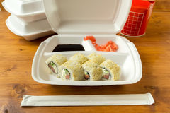 Container with sushi, ginger, soy sauce and set new chopsticks. Container with sushi, ginger, soy sauce and set new chopsticks on the wooden table Stock Images