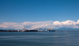 Container terminal. Container loading terminal near Vancouver, BC with cranes and mountains Stock Images