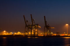 Container Terminal. A closer view of the container terminal in the harbor of Hamburg at night. Two stars in the sky. The lights are reflected by the water of the stock photos