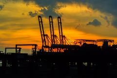 Container terminal of commercial industrial port at sunset. Gantry freight crane in container terminal of commercial industrial port at sunset for Logistic stock image