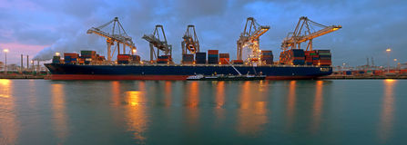 Container terminal at night. The activity of loading and unloading of huge container ships at the world's biggest and busiest container harbor in Rotterdam, just Royalty Free Stock Photo