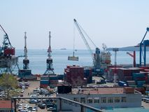 Container terminal port. Container terminal in Vladivostok harbor port. Business illustration demonstrating cranes loading freight on the ship Royalty Free Stock Images