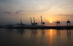 Container terminal and container ship on the Mekong river, Saigon port, Vietnam. View of the piers and cranes at sunrise. royalty free stock images