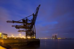 Container Harbor And Power Station At Night. A container terminal with tall cranes with a nuclear power station in the background. Night shot taken in Antwerp Stock Photo