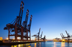 Container Terminals at Night. A large container harbor with deep blue night sky, taken with a shift lens Stock Photo