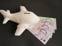 singaporean banknotes and white ceramic airplane for travel savings royalty free stock photography