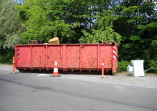 Container with trash at parkinglot plants in background Stock Photo