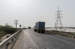 Container Truck on Kutch highway Gujarat, India. Container Truck on Kutch highway near Gandhidham surrounded by electric poles, salt industries and farms Gujarat Royalty Free Stock Images