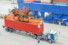 Container truck waiting for loading container box to Cargo ship Stock Image