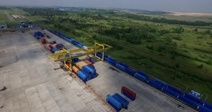 Container unloading Low-altitude airplane helicopter view of cargo train containers and rail lines in industrial stock video