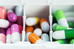 Container with various pills in different colors Stock Images