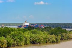 Container vessel sails upstream the Song Long River. Container vessel sails upstream the Song Long River from Vung Tau bay to Ho Chi Minh City through mangrove royalty free stock image