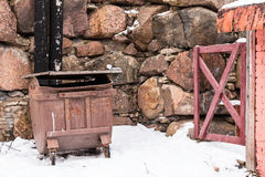 Container and wicket at wall. Garbage container and wicket near a stone wall in winter scene Stock Photography