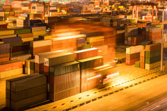 Container yard at night. Shipping container stack yard at night, light trails of industrial crane motion blur Royalty Free Stock Image