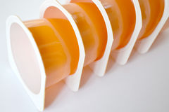 Container of yogurt. A few orange plastic containers for yogurt Stock Photo