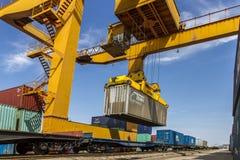 Containerized lasten för port den järnväg klänning Arkivbild