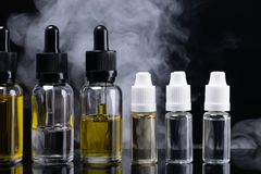 Containers of aromatic liquids on a black background surrounded by smoke. Six containers of aromatic liquids on a black background surrounded by smoke Stock Image
