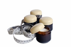 Containers with cosmetic cream and measuring tape Stock Photos