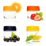 Containers of cream and fresh fruits and berries stock images