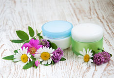 Containers with cream  and wild flowers Stock Photography