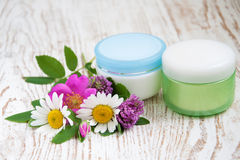 Containers with cream  and wild flowers Royalty Free Stock Images