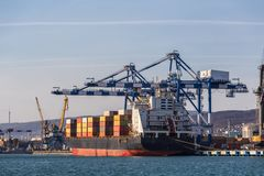 Containers on freight ship in industrial sea port for shipping and logistic, cranes and other special equipment stock image