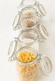 Containers full with pasta, rice, chickpeas. Healthy food ingredients. Royalty Free Stock Photo