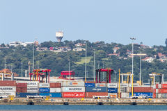 Containers in Harbor Against Residential District on the Bluff Stock Photo