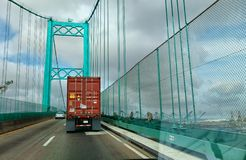 A truck pulling a cargo container drives over the Saint Thomas Bridge and over the Port of Los Angeles. royalty free stock image