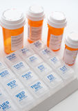 Containers with pills and weekly organizer. Vertical Stock Photos
