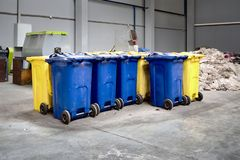Containers with shredded plastic prepared for further processing remelting and recycling with shredder in background stock photo